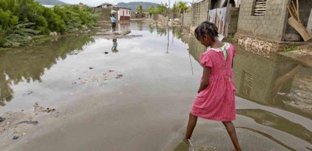 A girl walks through the flooded streets of her neighbourhood in Cap-Haïtien, Haiti, 2012. (Logan Abassi/UN Photo)