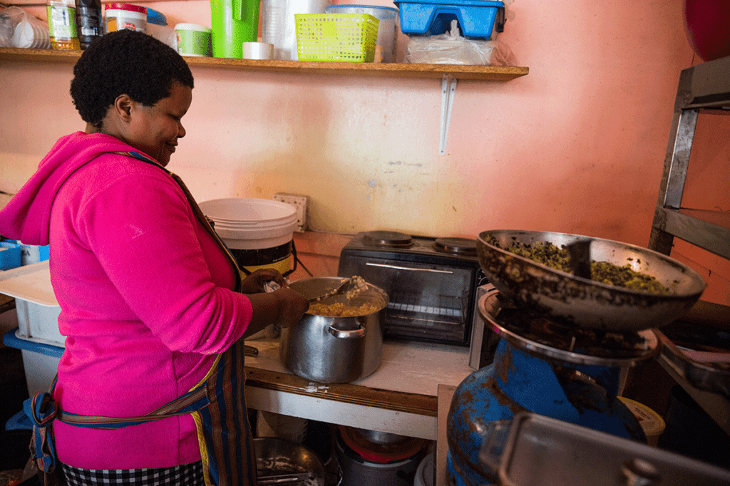 A resident from Masiphumele prepares food in her home.